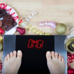 "Digital scales with woman feet on them and sign""OMG!"" surrounded by christmas decorations, sweets and alcohol. Demonstrates consequences of surfeit and eating unhealthy food during Christmas holidays."