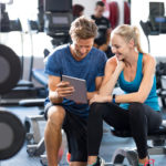 Smiling personal trainer using digital tablet while talking to b
