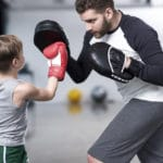 Become a life coach: young boy boxer practicing punches with coach